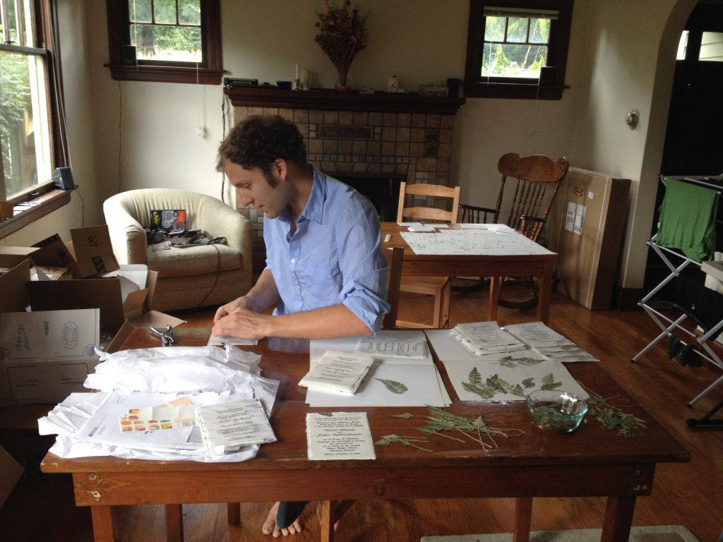 Seattle couple assembles Of The Earth invitations at home.
