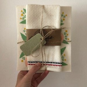hand holding a jute wrapped dishtowel with a green gift tag
