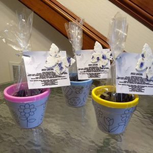 three lavender flower pots on a glass table with dirt in plastic bags and flower seed paper butterflies attached