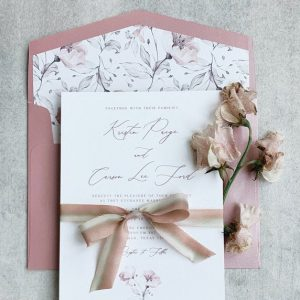 pink toned wedding invitation with sweet peas and ribbon